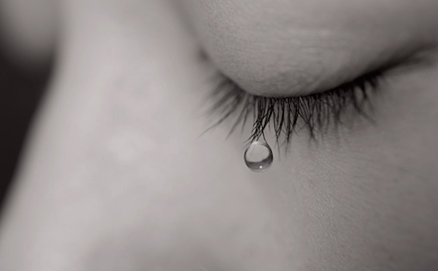 Young woman crying with tear drop